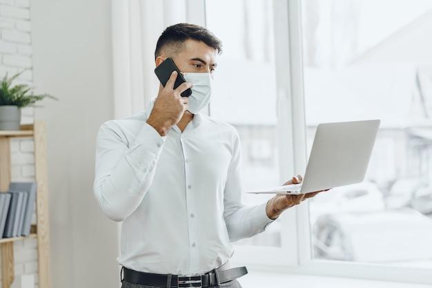 Homem de negócios bonito com máscara médica usando seu laptop enquanto fala ao celular