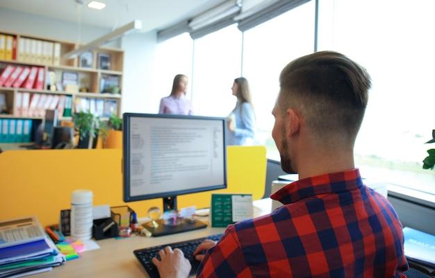Homem de negócios bonito com roupa casual em plano de fundo de seus sócios no escritório criativo