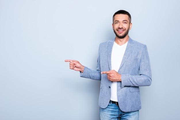 Homem de negócios bonito com uma jaqueta azul posando contra a parede azul clara