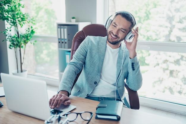 Homem de negócios bonito com uma jaqueta azul, trabalhando no escritório