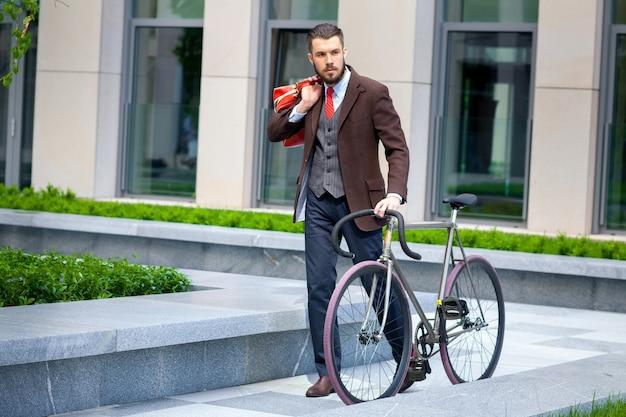 Homem de negócios bonito com uma jaqueta e gravata vermelha e sua bicicleta nas ruas da cidade. o conceito de estilo de vida moderno dos jovens