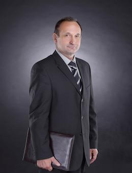 Homem de negócios bonito com uma pasta de couro isolada em preto