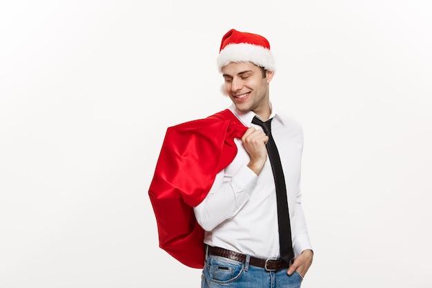 Homem de negócios bonito comemorar o feliz natal com chapéu de papai noel com saco grande vermelho de papai noel.