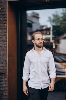 Homem de negócios bonito de camisa branca andando na rua
