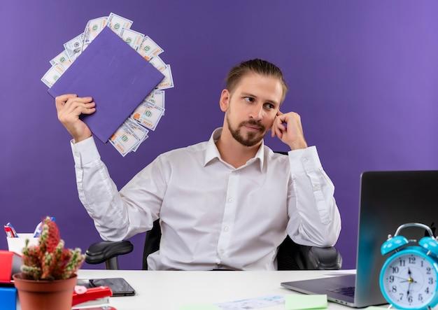 Homem de negócios bonito de camisa branca segurando pasta com dinheiro olhando para o lado com expressão pensativa, sentado à mesa em escritório sobre fundo roxo