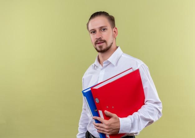 Homem de negócios bonito de camisa branca segurando pastas, olhando para a câmera com expressão confiante em pé sobre fundo verde-oliva