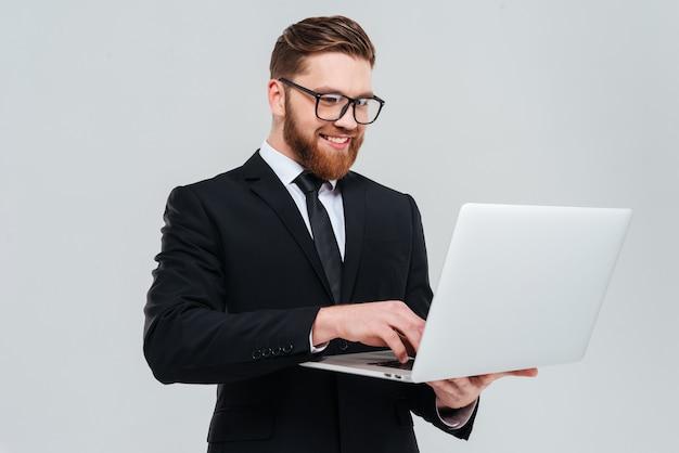 Homem de negócios bonito de óculos e terno segurando laptop nas mãos e escrevendo algo.
