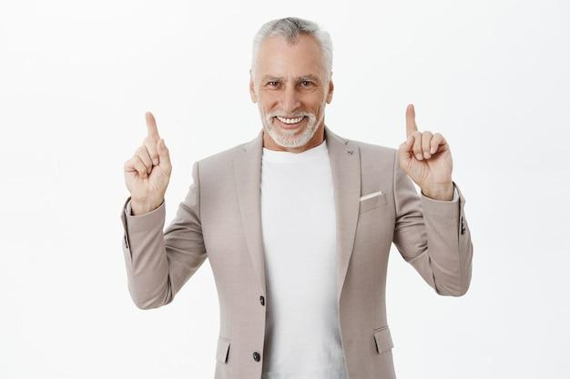 Homem de negócios bonito de terno apontando os dedos para cima e sorrindo satisfeito