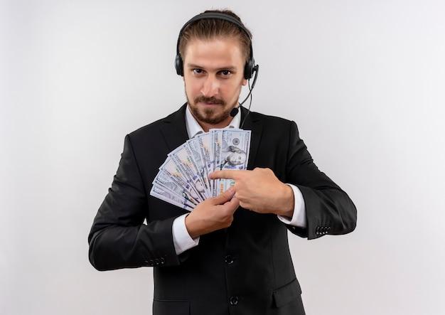 Homem de negócios bonito de terno e fones de ouvido com um microfone mostrando dinheiro apontando com o dedo para ele, olhando para a câmera com um sorriso no rosto em pé sobre um fundo branco