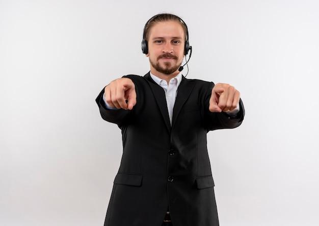 Homem de negócios bonito de terno e fones de ouvido com um microfone olhando para a câmera apontando os dedos para ela sorrindo em pé sobre um fundo branco