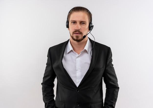 Homem de negócios bonito de terno e fones de ouvido com um microfone olhando para a câmera com expressão confiante em pé sobre um fundo branco