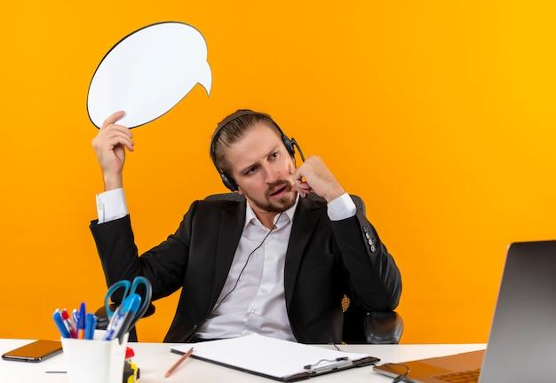 Homem de negócios bonito de terno e fones de ouvido com um microfone segurando um cartaz de balão de fala em branco, olhando de lado perplexo, sentado à mesa em escritório sobre fundo laranja