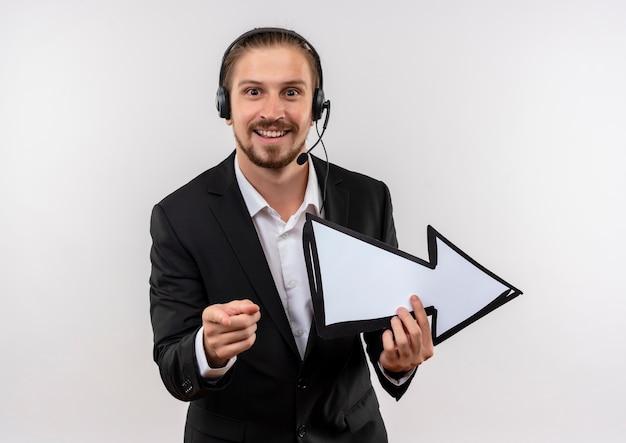 Homem de negócios bonito de terno e fones de ouvido com um microfone segurando uma seta branca apontando com o dedo para a câmera, sorrindo em pé sobre um fundo branco