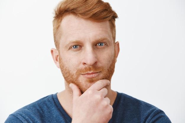 Homem de negócios bonito e inteligente ouvindo um conceito interessante de empregador, gostando de uma nova ideia, esfregando a barba com a mão e olhando fixamente enquanto pensa ou faz sua própria opinião