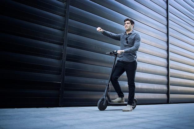 Homem de negócios bonito e positivo numa scooter elétrica, segurando o braço para a frente