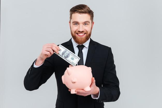 Homem de negócios bonito e sorridente de terno colocando dinheiro no cofrinho
