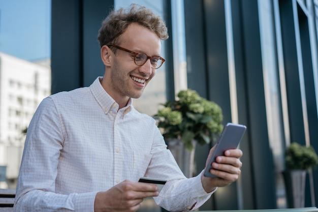 Homem de negócios bonito e sorridente segurando um cartão de crédito usando aplicativo móvel, compras online