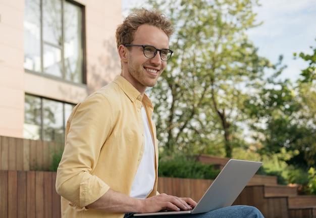 Homem de negócios bonito e sorridente usando óculos e usando laptop, planejando começar a trabalhar em casa
