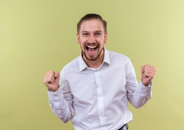 Homem de negócios bonito em camisa branca cerrando os punhos feliz e animado regozijando-se com seu sucesso em pé sobre fundo verde-oliva