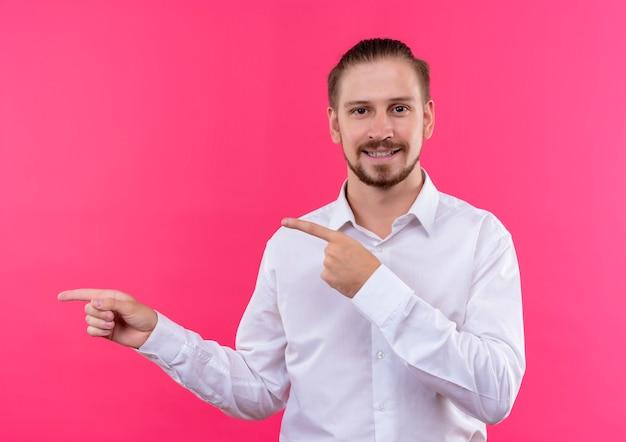 Homem de negócios bonito em camisa branca olhando para a câmera sorrindo apontando com o dedo indicador para o lado em pé sobre fundo rosa