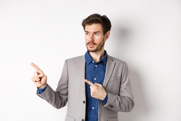 Homem de negócios bonito em terno apontando, olhando para a esquerda no logotipo com cara séria, de pé contra um fundo branco.