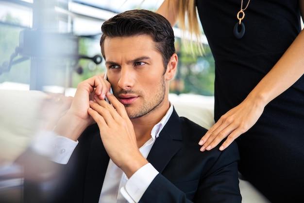 Homem de negócios bonito falando ao telefone em restaurante