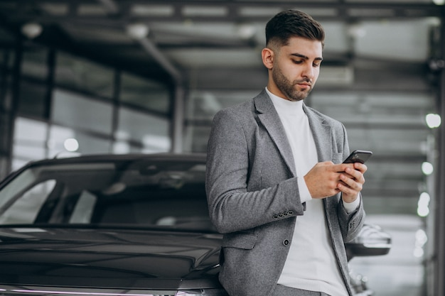 Homem de negócios bonito falando ao telefone em uma sala de exposições de carros