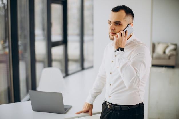 Homem de negócios bonito falando ao telefone no escritório