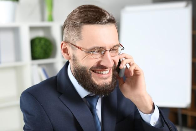 Homem de negócios bonito falando no celular dentro de casa