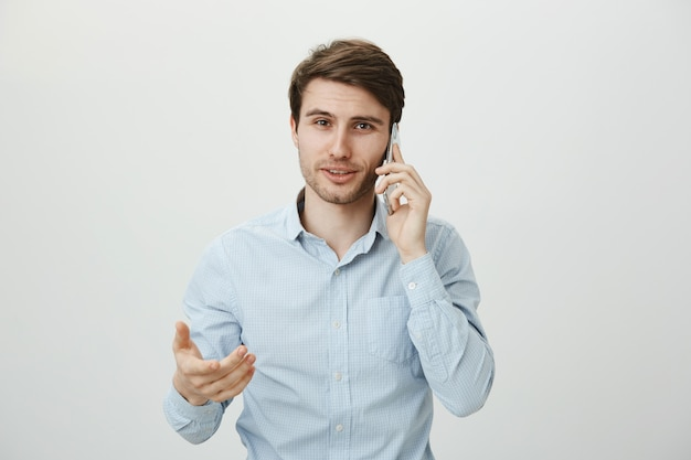 Homem de negócios bonito gesticulando durante uma conversa ao telefone