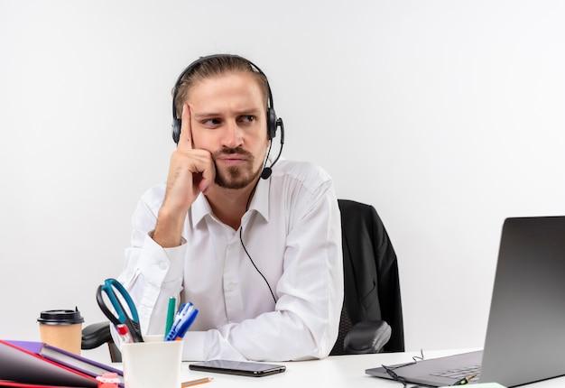 Homem de negócios bonito incomodado com camisa branca e fones de ouvido com microfone, ouvindo um cliente com cara séria sentado à mesa em escritório sobre fundo branco