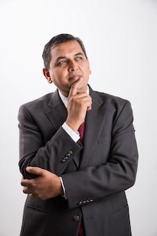 Homem de negócios bonito indiano ou asiático de meia idade em terno preto pensando ou tentando descobrir uma solução enquanto está isolado sobre um fundo branco