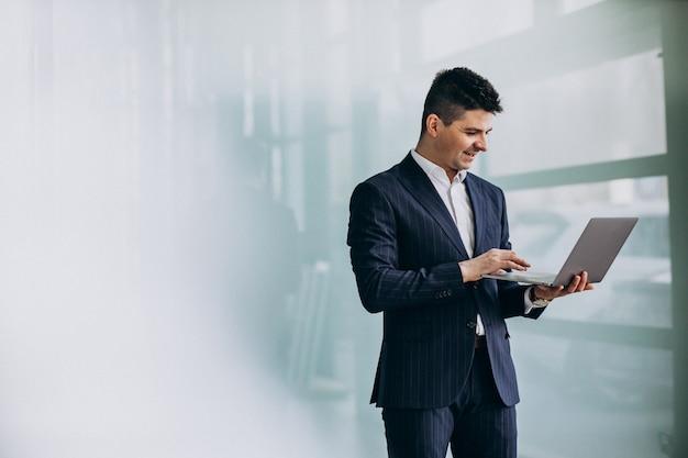 Homem de negócios bonito jovem com laptop no escritório