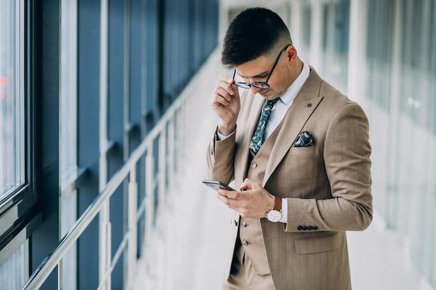 Homem de negócios bonito jovem de pé com telefone no escritório