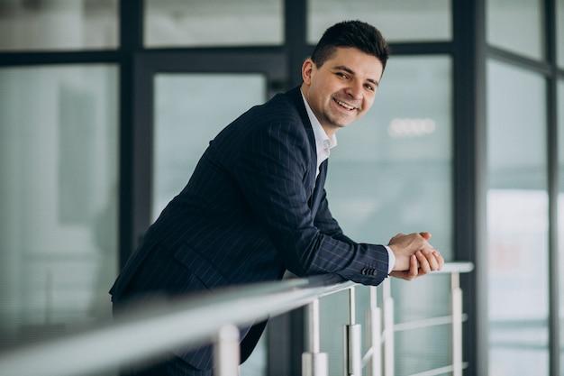 Homem de negócios bonito jovem de terno em um escritório