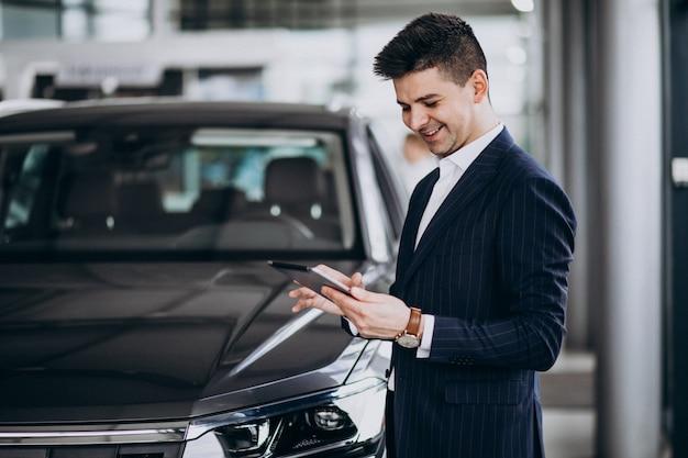 Homem de negócios bonito jovem em um carro showrrom