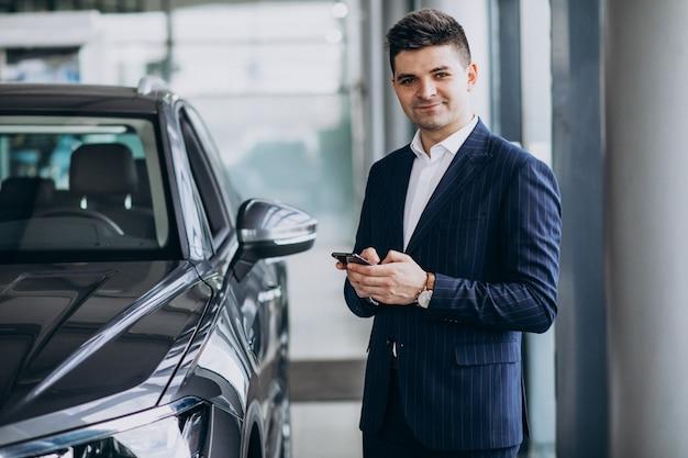 Homem de negócios bonito jovem em uma sala de exposições de carro, escolhendo um carro