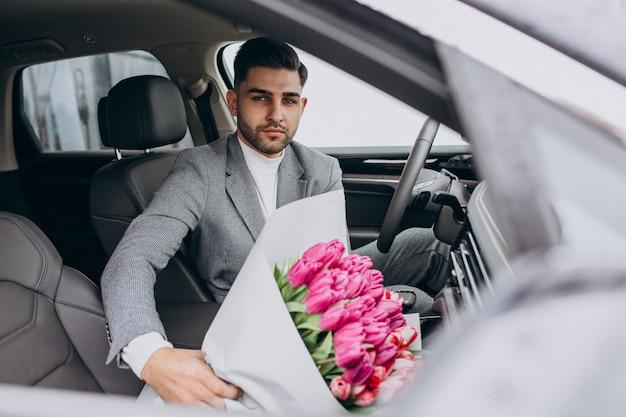 Homem de negócios bonito jovem entregando buquê de flores lindas
