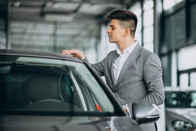 Homem de negócios bonito jovem escolhendo um carro em uma sala de exposições de carros