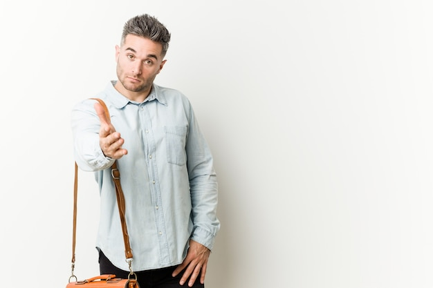 Homem de negócios bonito jovem esticando a mão na câmera em gesto de saudação