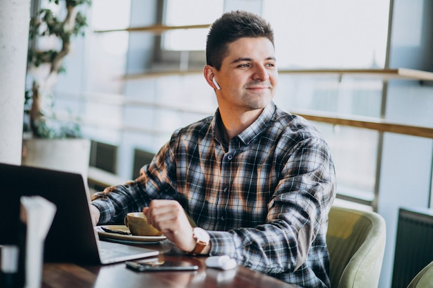 Homem de negócios bonito jovem usando laptop em um café