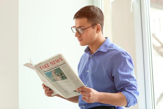 Homem de negócios bonito lendo jornal no escritório