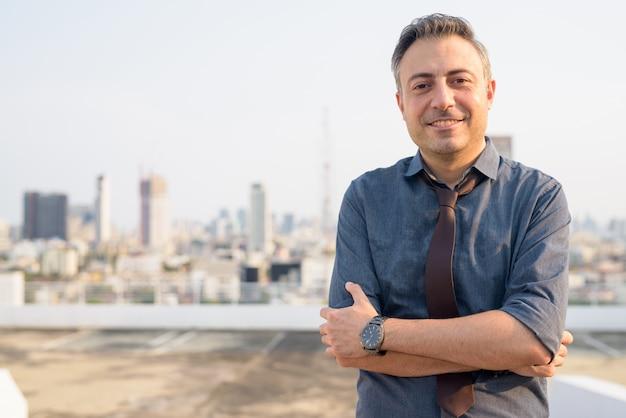 Homem de negócios bonito maduro feliz sorrindo com os braços cruzados na cidade