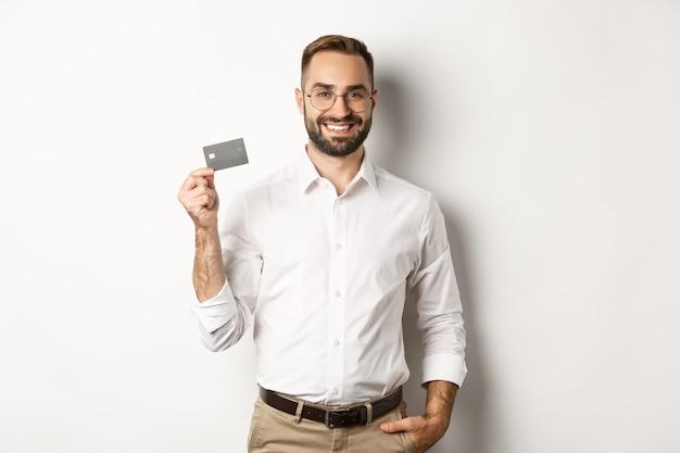 Homem de negócios bonito mostrando seu cartão de crédito, parecendo satisfeito, de pé