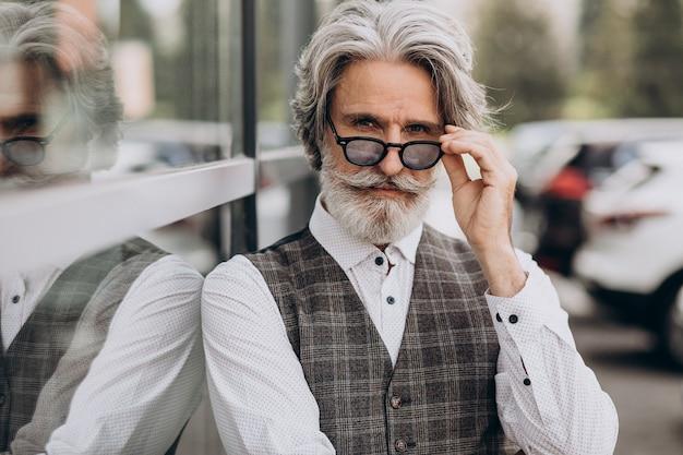 Homem de negócios bonito parado do lado de fora pensando