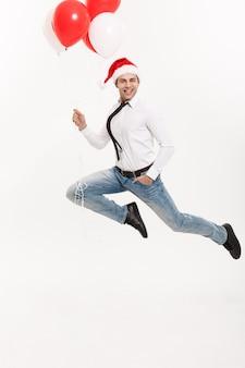 Homem de negócios bonito pulando para comemorar o feliz natal, usando chapéu de papai noel com balão vermelho.