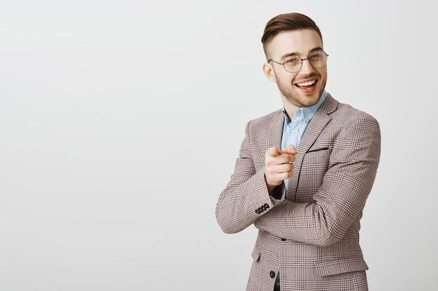 Homem de negócios bonito satisfeito apontando para uma pessoa que está defendendo seu ponto de vista, bom trabalho, elogiando o funcionário e dizendo bem feito
