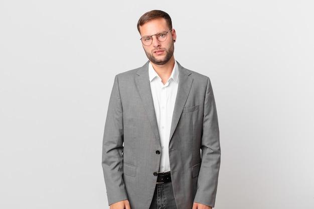 Homem de negócios bonito se sentindo perplexo e confuso