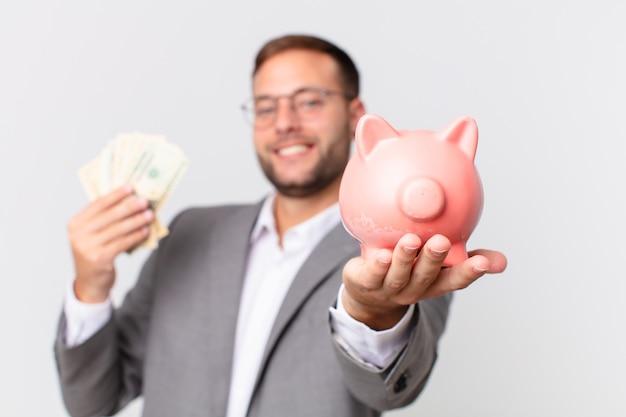 Homem de negócios bonito segurando um cofrinho. conceito de economia