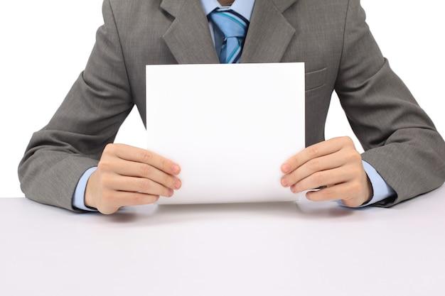 Homem de negócios bonito segurando um quadro branco e apontando, olhando para a câmera e sorrindo, isolado no branco, estúdio tiro